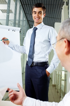 new strategy: Smiling businessman presenting new strategy to his senior associate