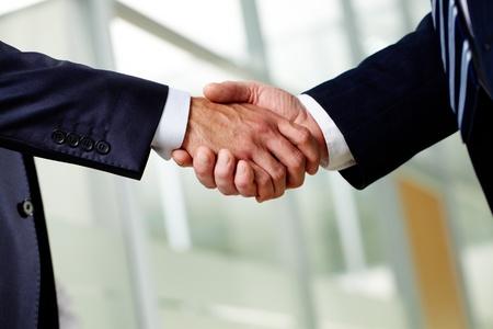 契約締結を成功のサインと握手を交わして上級ビジネスマン
