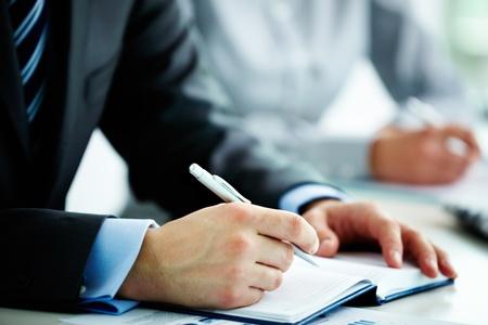 摘要: 男性的手像用鋼筆在打開筆記本的研討會