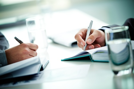 executive courses: Image of male and female hands with pens over open notebooks at seminar