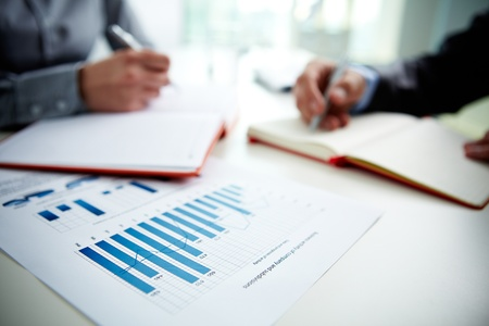 economy: Image of document with charts on background of male and female hands with pens over open notebooks at seminar Stock Photo