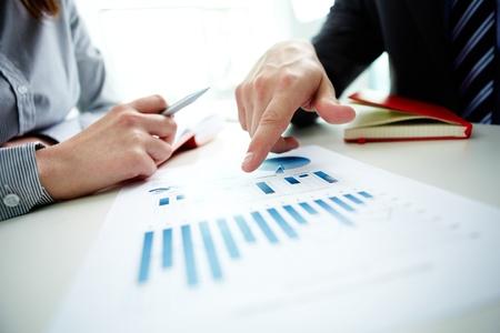 Afbeelding van mannelijke hand te wijzen op zakelijk document tijdens de discussie in de vergadering