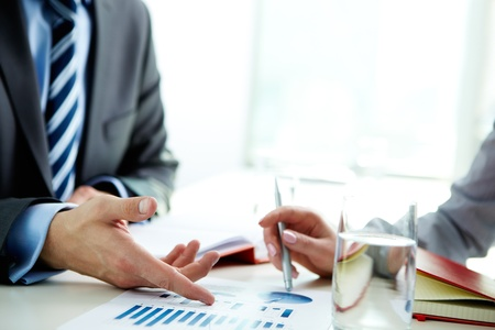 financial success: Image of male hand pointing at business document during discussion at meeting Stock Photo
