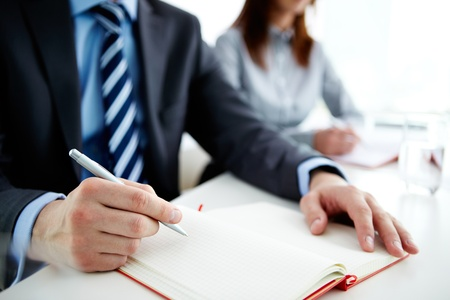 summary: Image of male hand with pen over open notebook at seminar or lecture Stock Photo