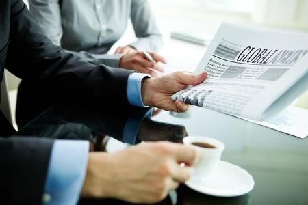 Immagine della mano maschile con il giornale e la tazza di caffè