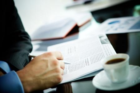 Afbeelding van mannelijke hand met pen en krant en kopje koffie in de buurt van