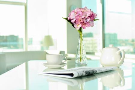 papeles oficina: Lugar de trabajo con, taza de porcelana y la olla de peri�dicos y ramo de flores Foto de archivo