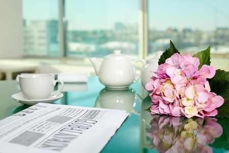 Table with porcelain cup and pot, newspaper and bunch of flowers on it photo