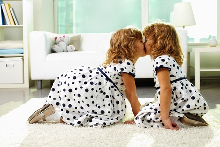 Portrait of happy twin girls kissing at home photo