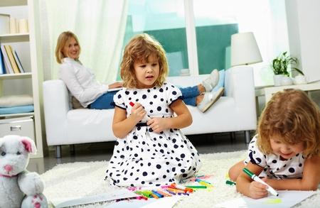 niñas gemelas: Retrato de dos niñas gemelas de dibujo en su casa con su madre se relaja en un sofá en el fondo Foto de archivo