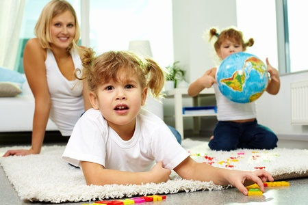 Portrait of cute girl looking at camera with her mother and twin sister on background Stock Photo - 12620399