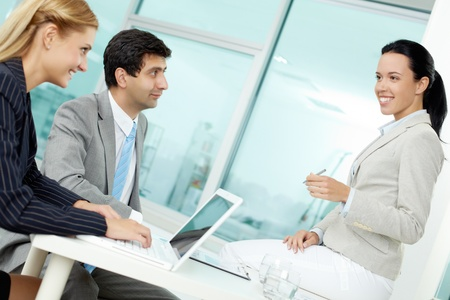 Three business people discussing ideas at workplace in office Stock Photo - 12620543