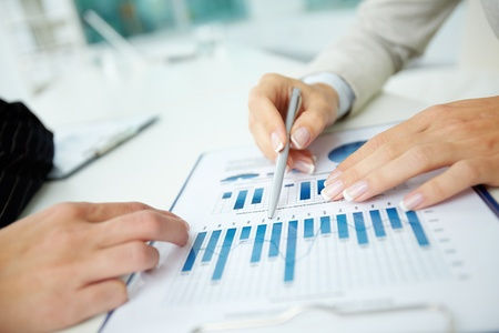 recursos financieros: Imagen de las manos femeninas con las plumas más de documento de negocio en una reunión
