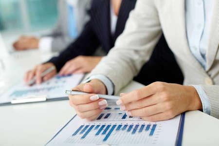 Primer plano de las manos femeninas con la pluma sobre el documento comercial en el entorno de trabajo