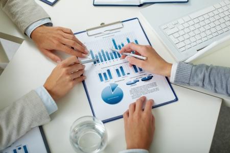 recursos financieros: Imagen de las manos del hombre con las plumas que señalan en el documento de negocio a satisfacer las Foto de archivo