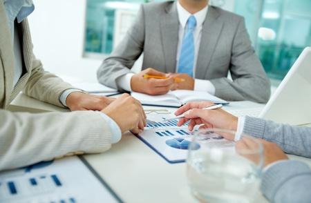 Image de mains féminines avec des stylos plus des documents commerciaux sur le fond de leur patron