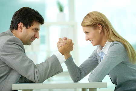 Man and woman in arm wrestling gesture on working table during meeting Stock Photo - 12620411