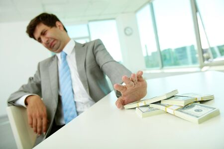 bribe: Image of disgusted male employee moving dollar bills away and refusing to take bribe Stock Photo