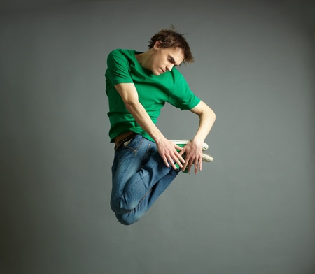 hover: Guy in casual outfit performing a tricky twisted jump Stock Photo