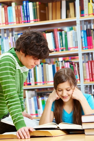 Schoolboy standing near his friend in library while she reading book with a smile photo