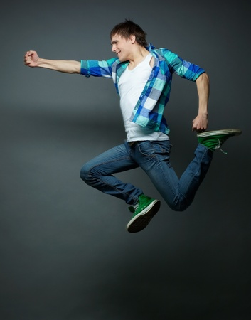 one young man: Energetic guy jumping with fists clenched tight and kicking the air