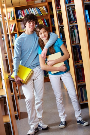 Tilt up shot of teenage couple standing together at library and smiling at camera photo