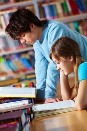 Young people studying together at library reading books photo