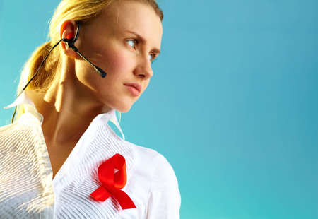 Portrait of pretty woman with headset and red ribbon on blouse over blue background Stock Photo - 12620402