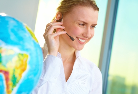 support agent: Portrait of smiling tour agent with headset consulting client online