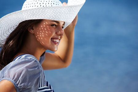 brim: Pretty woman laughing and holding the brim of the hat sitting in the sun