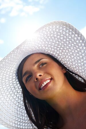 Vertical tilt up shot of smiling summer girl in white woven hat  photo
