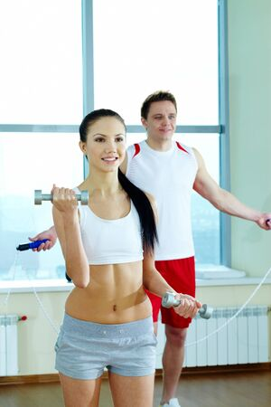 Image of fit woman doing exercise with barbells with young guy on background photo