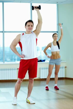 Image of young man doing exercise with barbells with pretty girl on background photo