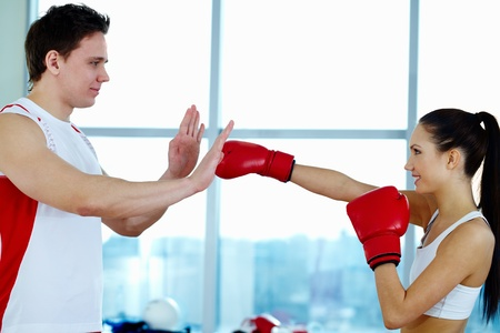Portrait of young woman in red boxing gloves showing attack grip to trainer  photo