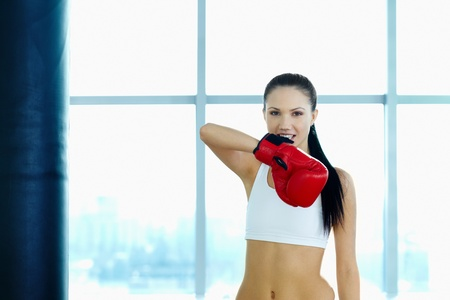 Portrait of young woman in red boxing gloves looking at camera in gym  photo