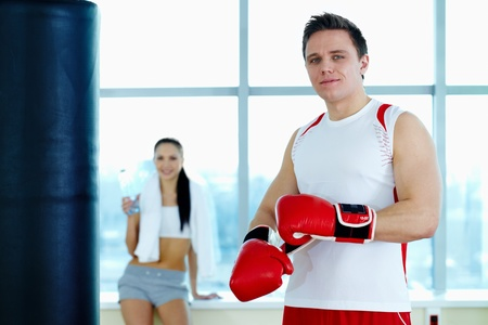 Portrait of young man in red boxing gloves looking at camera in gym  photo