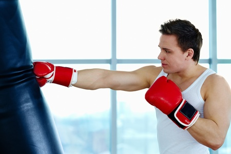 Portrait of young male boxer training in gym  photo
