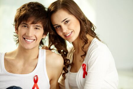 Smiling guy and girl with red ribbon badges sitting together and looking at camera Stock Photo - 12620416