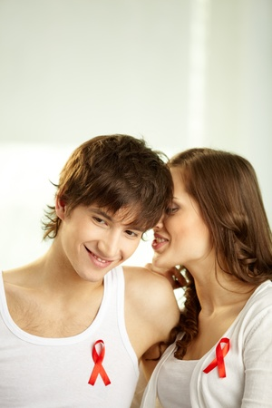 Girl whispering some secrets in her boyfriend's ear, red ribbons attached to their clothing photo