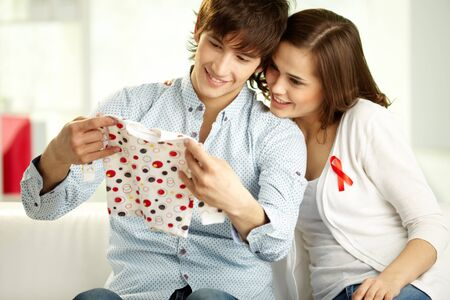 Young couple holding tiny baby clothes and looking at it with a smile photo