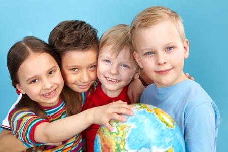 Schoolkinderen met een wereldbol kijken naar de camera positief Stockfoto
