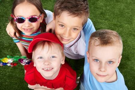 wiatrowskaz: Chłopców i dziewczyna patrząc na kamery, dziewczyna ma na sobie okulary i trzyma łopatki