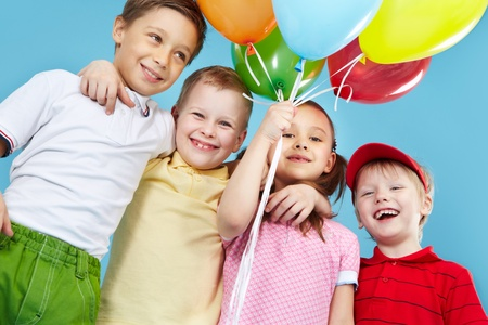 kids birthday party: Cheerful kids holding a bunch of colorful balloons