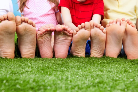 pies masculinos: Los amigos felices que se sientan en la hierba descalzo