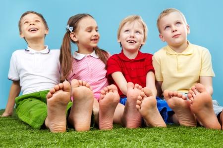 bambini seduti: Bambini felici seduto sul prato a piedi nudi