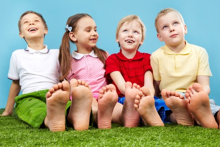 human toe: Happy children sitting on the lawn barefoot Stock Photo