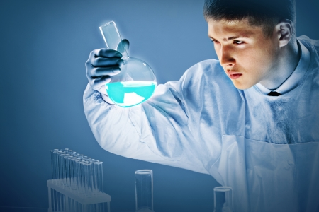 young male doctor: Young scientists looking closely at luminous blue liquid poured in a beaker