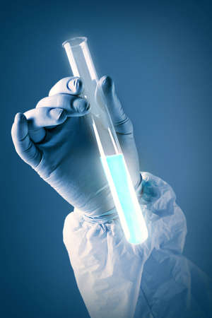 reagent: Vertical shot of gloved hand holding a glass tube full of reagent Stock Photo