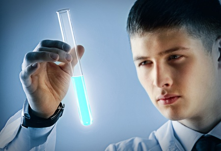 reagent: Young scientist looking seriously at a tube with luminant reagent Stock Photo