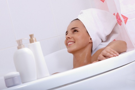 Tilt up of attractive girl with towel on her head lying in bathtub and smiling photo